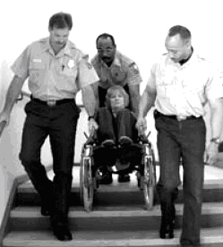 Black and white photograph showing the correct technique for assisting the evacuation of a person who uses a wheelchair. U.S. Fire Administration 'Orientation Manual for First Responders on the Evacuation of People with Disabilities'. FA-235/August 2002.