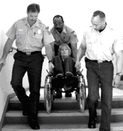 Black and white photograph (US FEMA 2002) showing the correct way to assist the fire evacuation of a wheelchair user in an evacuation staircase ... one person at each side, with another person behind.