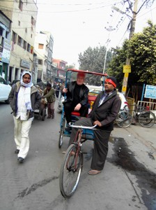Colour photograph showing a silly tourist on a bicycle rickshaw, as he is brought sightseeing around the Bazaar District in Old Delhi. Click to enlarge. Photograph taken by Mr. Daljeet Singh, Ministry of Tourism, with CJ Walsh's camera. 2010-01-09.