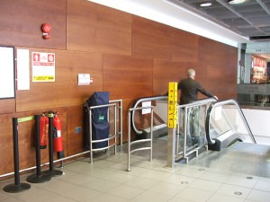 Colour photograph showing a Fire Evacuation Chair Device Installation at Dublin Airport, Ireland. On so many levels and in so many ways, this 'decorative' installation ... intended to demonstrate that an organization is complying with legislation ... will prove to be, in the event of a real fire emergency, SO wrong and unworkable. Photograph taken by CJ Walsh. 2008-04-04. Click to enlarge.