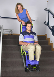 Colour photograph showing a Manual/Gravity Fire Evacuation Chair Device in operation. Transfer from a wheelchair to this type of device at the top of a staircase can be difficult and hazardous ... it can only travel down a staircase, using gravity (never up, against gravity !) ... and during horizontal travel, it is shaky and unstable. Click to enlarge.