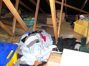 Colour photograph showing the typical clutter which can accumulate, over time, in an Attic Roof Space. Wait and see, however, what else is happening underneath and around this clutter. Smoke Detectors should always be fitted in these Spaces as a matter of routine. Also ... notice that this is a trussed timber roof. Photograph taken by CJ Walsh. 2010-05-21. Click to enlarge.