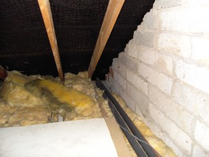 Colour photograph showing thermal insulation packed tightly into the roof eaves ... choking off essential ventilation pathways. Thermal insulation was also placed under the water storage tanks ... exposing them to freezing external conditions during cold winter nights. Thick, multi-layered thermal insulation will also conceal the bottom horizontal members in all types of timber roof construction ... expect more fall accidents through ceilings in the future! Photograph taken by CJ Walsh. 2010-05-21. Click to enlarge.