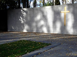 Colour photograph showing, in the background, a latin cross and the Irish language version of the 1916 Proclamation of Independence inscribed on the stone wall, with the simple grass-covered graves of Executed Leaders in the foreground. Detail of the 1916 Revolution Memorial in Arbour Hill Cemetery, Dublin. Photograph taken by CJ Walsh. 2010-10-24. Click to enlarge.