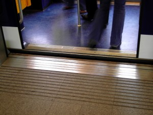 Colour photograph showing the Door Threshold Detail of the new, automatically operated CDGVAL Métro at Roissy Charles De Gaulle Airport in Paris. In totally new construction ... an unacceptably huge difference between platform height and the shuttle's floor ! This is also now a trip hazard for everyone !! Photograph taken by CJ Walsh. 2010-11-26. Click to enlarge.