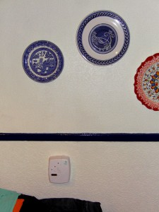 Colour photograph showing a battery-operated Ei Electronics Carbon Monoxide (CO) Detector, Model Ei206D, fixed (tamper proof) to the kitchen wall. Two of the hanging decorative plates are from France and Turkey. As for the third plate ... does anyone remember the Willow Pattern ? Photograph taken by CJ Walsh. 2011-01-12. Click to enlarge.
