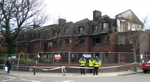 Colour photograph showing the cordoned-off scene in the aftermath of the fires at a Terrace of Housing in Terenure, Dublin City. In the foreground, Gardaí are keeping a watchful eye. Photograph taken by CJ Walsh. 2011-04-04. Click to enlarge.