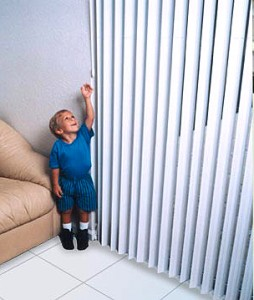 Colour photograph showing a small child reaching for the control wand of a Vertical Window Blind in familiar surroundings, for example, at home. This is just one of a range of Child Safe Window Covering Solutions.