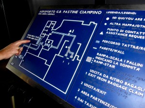 Colour photograph showing a Large Tactile Floor Plan at one of the entrances to the terminal building at Ciampino Airport in Rome, Italy. Notice, in particular, the use of an easily understandable type font combined with the high contrast between white characters and blue background ... the presentation of information in three different languages: Italian, English and Braille ... and, finally, the panel is mounted at a convenient height and angle. Photograph taken by CJ Walsh. 2011-10-26. Click to enlarge.