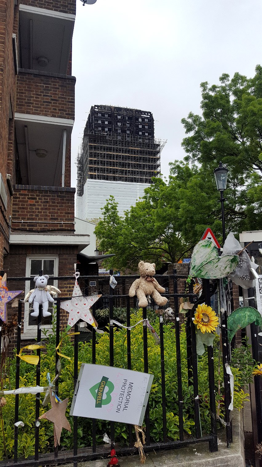 Ar Cj Walsh Consultant Architect Fire Engineer Technical Solar Panel Circuit The Heads On Community Colour Photograph Showing Grenfell Tower In Background Undergoing An Almost Complete Cover Up With Foreground Mementos Of